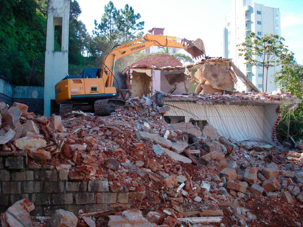 demolição de uma casa em porto belo com uma retrosecavadeira amarela
